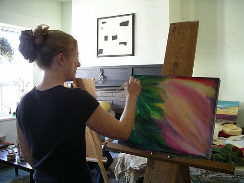Kendra Dixson (Smith) painting an intuitive acrylic painting at an easel.